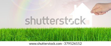 Concept white paper house held in hand by a man in a green summer grass over a rainbow sky background with clouds banner a symbol for construction, eco, ecology, loan, mortgage, property or home - stock photo