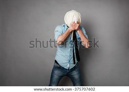 concept with a young man with face covered by a textile material covering his mouth, on grey - stock photo