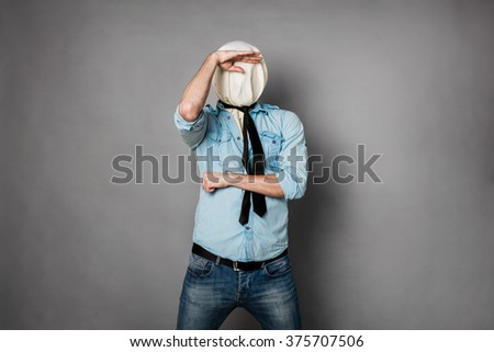 concept with a young man with face covered by a textile material looking - stock photo