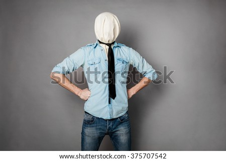 concept with a young man with face covered by a textile material posing, on grey - stock photo