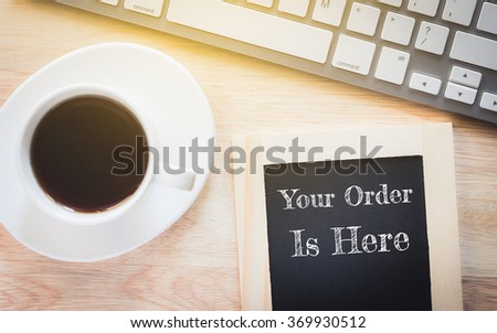 Concept Your Order Is Here message on wood boards. A keyboard and a glass coffee table.Vintage tone. - stock photo