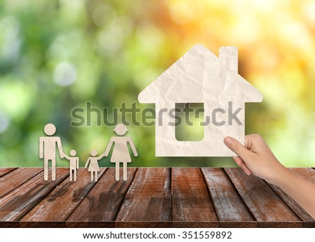 Concepts of Hand put House and family on Wood table top
