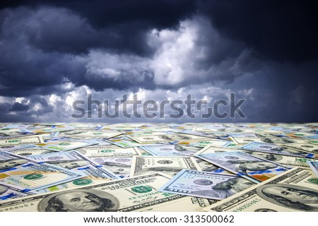 Conceptual abstract landscape: sea of money and dramatic sky. - stock photo
