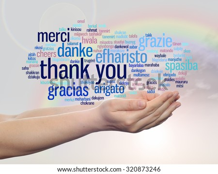 Conceptual abstract thank you word cloud held in hands in different languages or multilingual over rainbow sky for education,Thanksgiving Day, appreciation, multicultural, friendship, tourism travel - stock photo