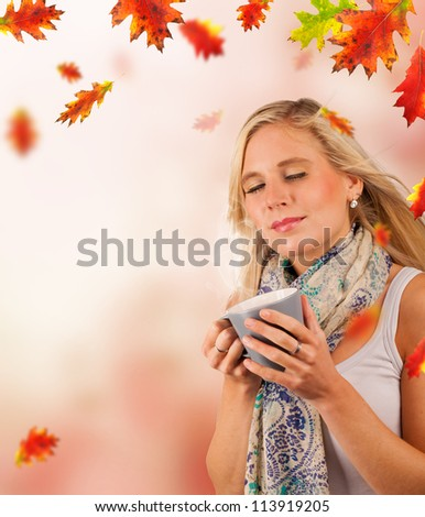 Conceptual autumn portrait of beautiful blond woman drinking tea with falling leaves around