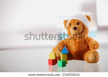 Conceptual Bandaged Brown Teddy Bear with Colored Block Shapes on Top of the Table - stock photo
