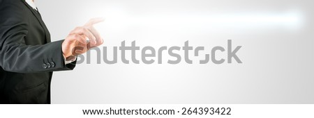 Conceptual Businessman in Black Business Suit Clicking a Glowing Light on a Grey Background, Emphasizing Copy Space. - stock photo
