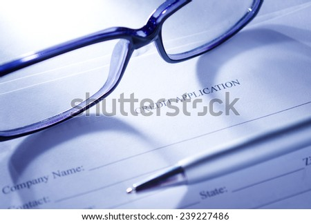 Conceptual Close up of Unisex Eyeglasses and Ballpoint Pen on Top of Blank Credit Application Form Paper. - stock photo