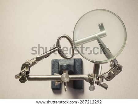 Conceptual composition, finding the solution, key as symbol, magnified with an old tool for soldering.  - stock photo