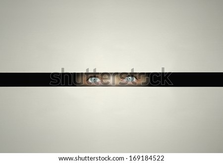 Conceptual eyes watching throw a slit with curiosity in the darkness  - stock photo