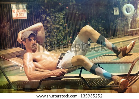 Conceptual fashion portrait of a sexy handsome man at the pool with a nostalgic retro distressed treatment and toning