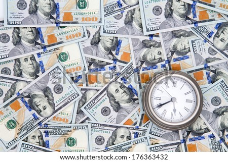Conceptual financial background of American 100 dollar bills with Benjamin Franklin facing upwards and a vintage watch depicting time - stock photo