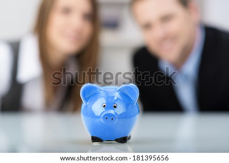 Conceptual financial image with a cute blue ceramic piggy bank sitting centered on a desk with a smiling successful professional couple in the background, focus to the piggy - stock photo
