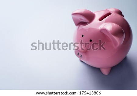 Conceptual financial image with a high angle view of a pink ceramic piggy bank with focus to the coin slot on its back over a grey background with copyspace - stock photo