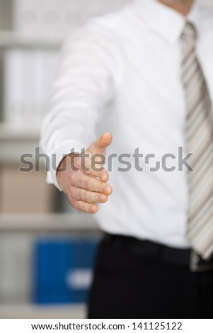 Conceptual gesture of business handshake over the blurred background - stock photo