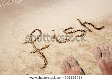 Conceptual hand made or handwritten text in sand on a beach in an exotic island with feet for summer, ocean, sea, travel, vacation, tourism, tropical, coast, message, resort, paradise, sunny or water - stock photo