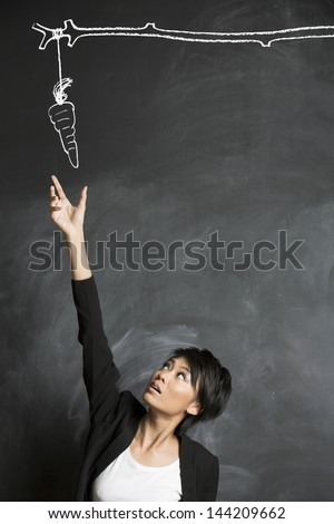 Conceptual image about motivation and reaching a goal. Carrot and Stick drawn with chalk on a blackboard. - stock photo