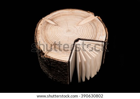 Conceptual image about the cross section of the tree trunk and book on black background. Tree Trunk and Book.