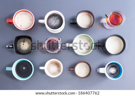 Conceptual image depicting the Time for your daily dose of caffeine with an overhead view of a neat arrangement of twelve different cups, mugs and glasses filled with hot fresh tea and coffee on grey - stock photo
