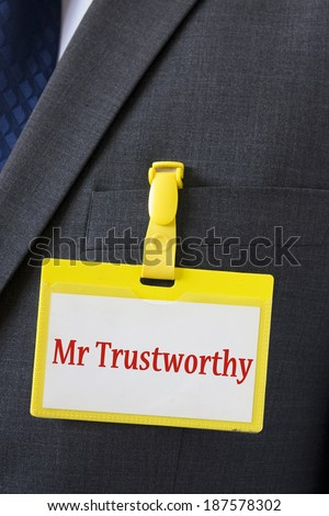 "Conceptual image form trust in business - name card on a dark suit with a sign saying ""Mr Trustworthy"" - stock photo"