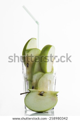 Conceptual image - fresh apple fruit in a glass on a white background. - stock photo