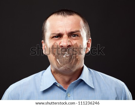 Conceptual image of a businessman with duct tape over his mouth - stock photo