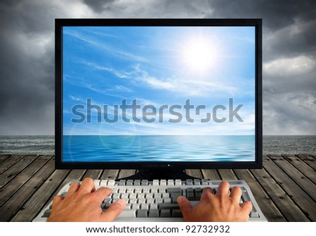 Conceptual image of a computer monitor and keyboard being operated outdoors by the seashore
