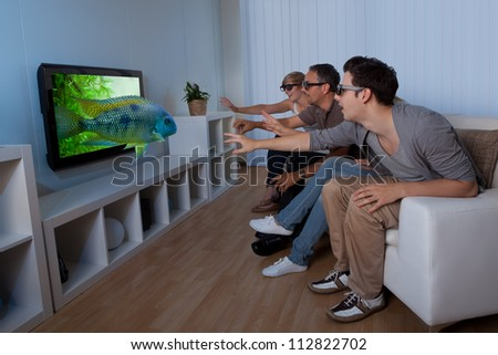 Conceptual image of a family watching 3D television and stretching out their hands as though to touch the image on the screen