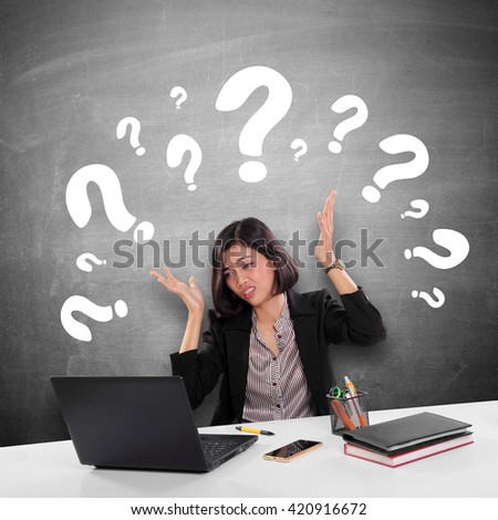 Conceptual image of a female office worker gets confused while doing her job, illustrated with many question marks above her head - stock photo
