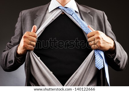 Conceptual image of a man tearing off his shirt over gray background - stock photo