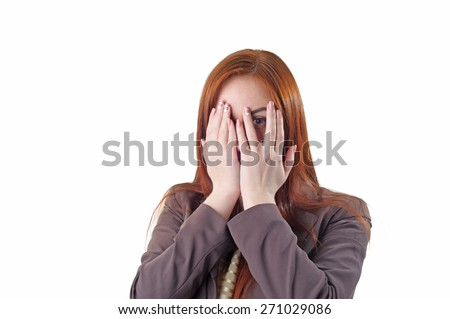 Conceptual image of a redhead woman covering her face with her hands and peering out with one eye between her fingers on a white background - stock photo