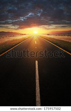 Conceptual image of a straight  asphalt road leading into the sunlight - stock photo