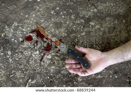 Conceptual image of a victim hand holding a sharp knife with blood on it resting on a concrete floor. Concept photo of murder and crime - stock photo