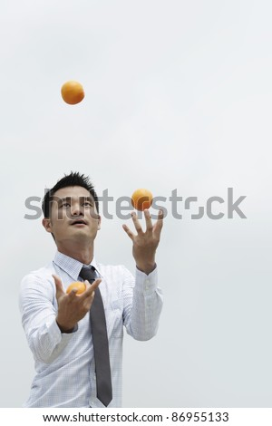 Conceptual image of an Asian Business man juggling oranges