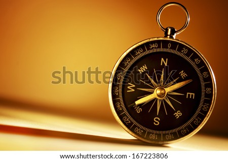 Conceptual image of an old brass handheld magnetic compass standing upright against a brown background with copyspace - stock photo