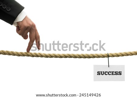 Conceptual image of business or life determination with a businessman walking his fingers along a length of rope or a tightrope towards success. - stock photo