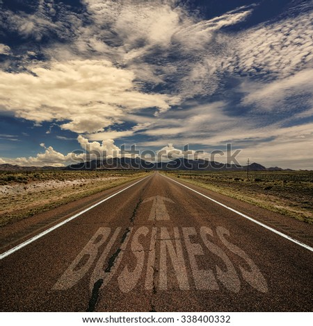Conceptual image of desert road with the word business and arrow - stock photo