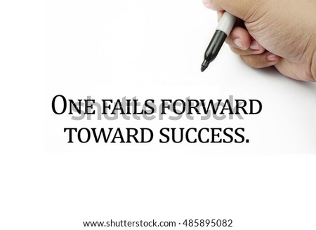 Conceptual image of handwriting quotes ONE FAILS FORWARD TOWARD SUCCESS with the hand and pen isolated in white background. copy space . Quotes concept.