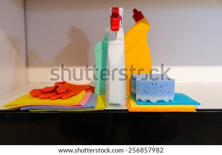 Conceptual image of hygiene and cleanliness in the house with a display of brightly colored cloths, a sponge rubber gloves and spray bottles on a kitchen counter - stock photo