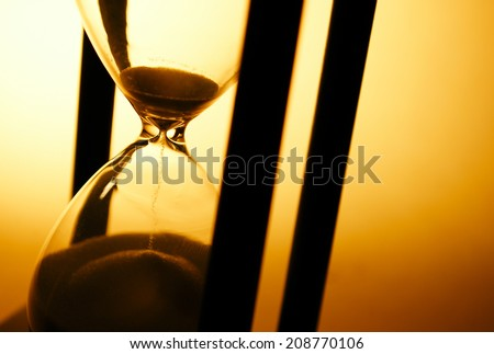 Conceptual image of measuring passing time with a close up view of sand running through an hourglass or egg timer on a golden background with copyspace - stock photo