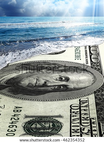 conceptual image of money on beach covering with waves of water.