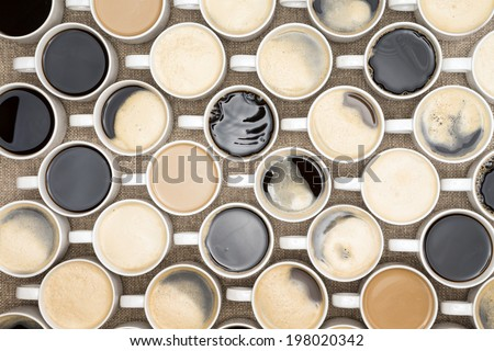 Conceptual image of regimented rows of coffee mugs lined up in straight rows with their handles facing the same direction like coffee soldiers, overhead view with black, espresso, latte and cappuccino - stock photo