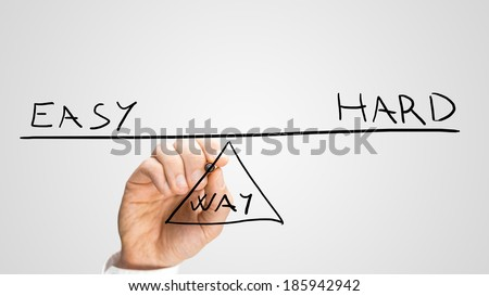 Conceptual image of the hand of a man drawing a seesaw in equilibrium with the text Easy - Hard - Way showing a balance between the two methods of reaching a solution.