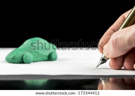 Conceptual image of the hand of a man signing a contract for the lease or purchase a green eco-friendly fuel efficient, electric or hybrid car with reduced carbon emissions - stock photo