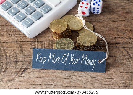 Conceptual image of the words Keep More Of Your Money written on label tag with coins,dice and calculator - stock photo