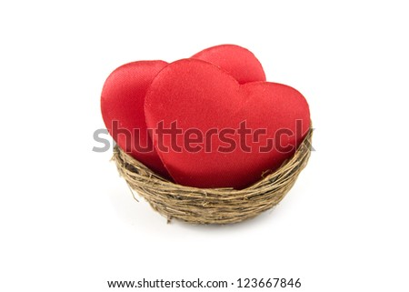 Conceptual image of two red hearts in a birds nest isolated on white background - stock photo