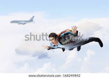 Conceptual image of young businessman flying with parachute on back - stock photo