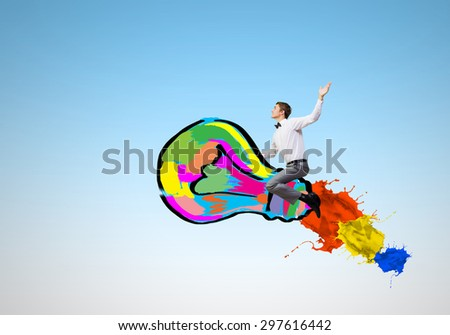 Conceptual image of young businessman riding light bulb