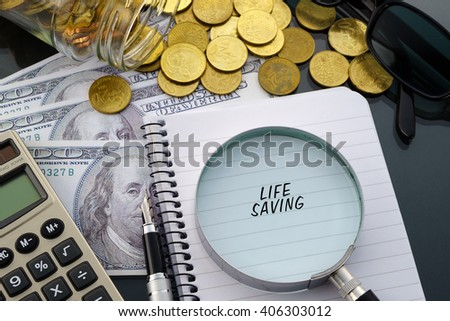 Conceptual image with hundred dollar bills, coins, calculator, notepad and magnifying glass with word Life Saving. - stock photo