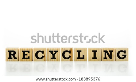 Conceptual image with the word - Recycling - in capital letters on a row of wooden blocks or cubes with a reflection below and white copyspace above. - stock photo